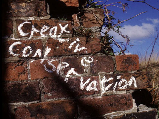 brick wall with creative conservation written on it